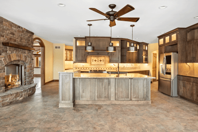A Kitchen Remodel With A Wooden Island and Fireplace in The Kitchen.