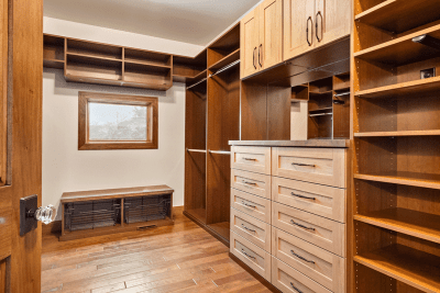 A Walk In Closet With a Small Window Towards the Back.