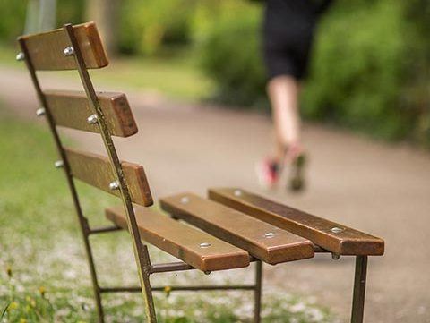 running person passing bench in park during jogging