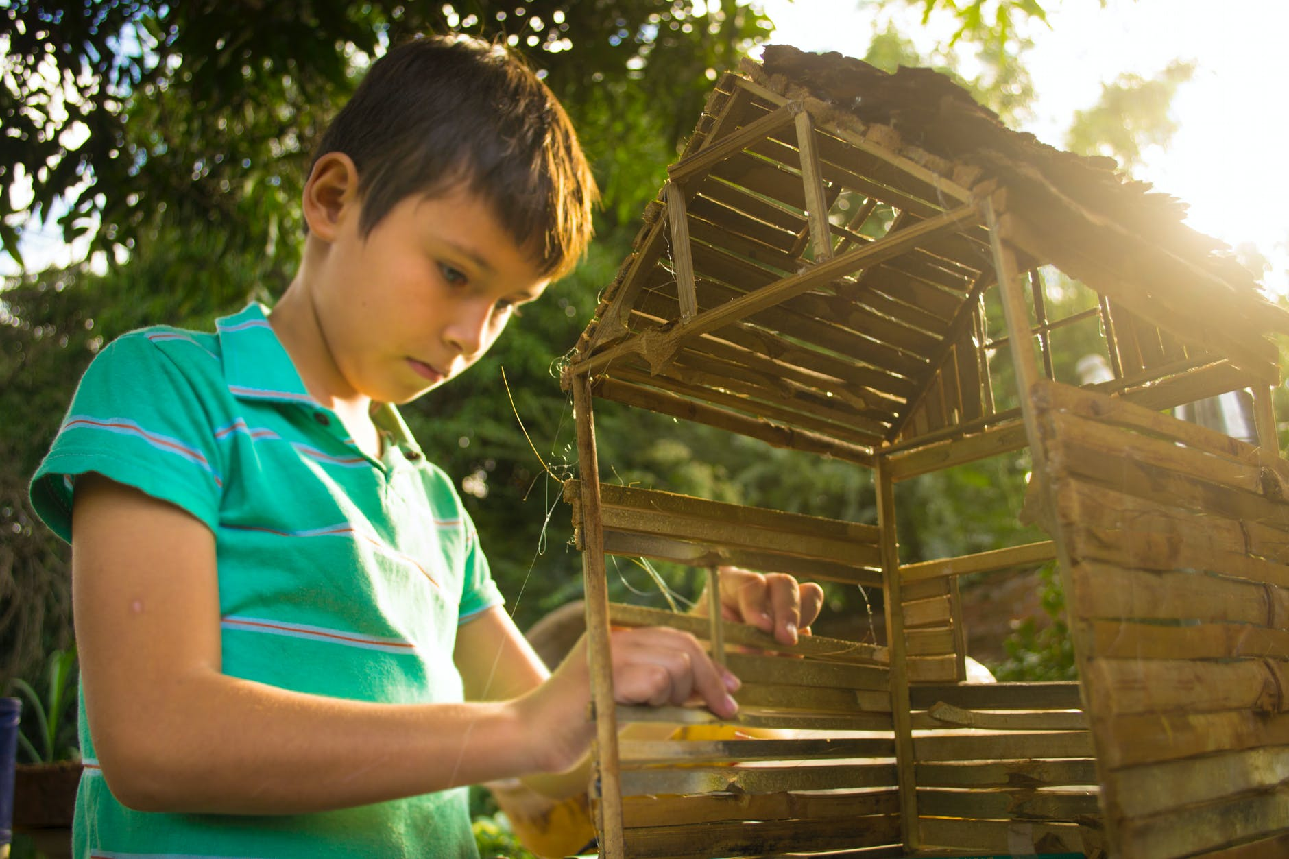 boy making wooden house miniature