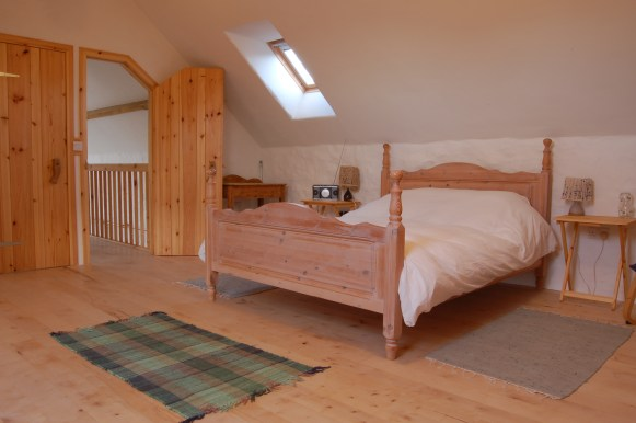 Harmony Barns spacious upstairs bedroom with lime plastered walls and organic bed linen, a cosy eco holiday cottage..