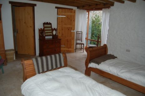 The twin bedroom of this self catering holiday cottage. Organic bed linen and en suite wet room.