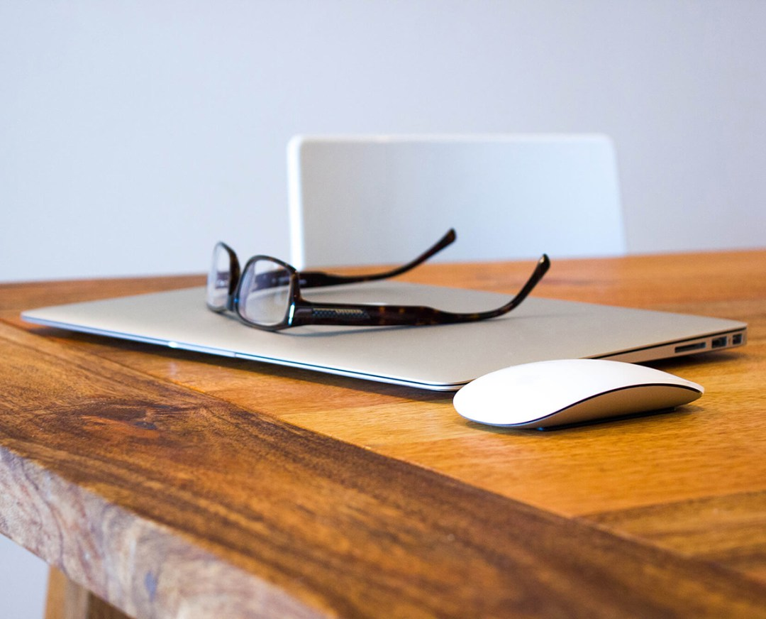 professional setting, desk with apple laptop with eye glasses on top