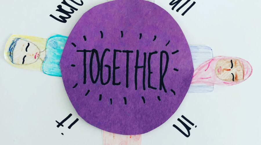 A pencil crayon and felt marker drawing of four girls, with the words, 'We're All in it Together.'