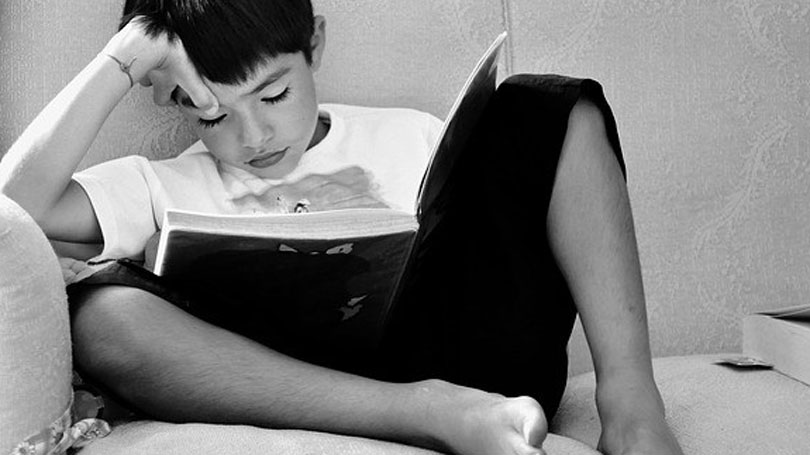 Child sitting reading after domestic violence and child abuse