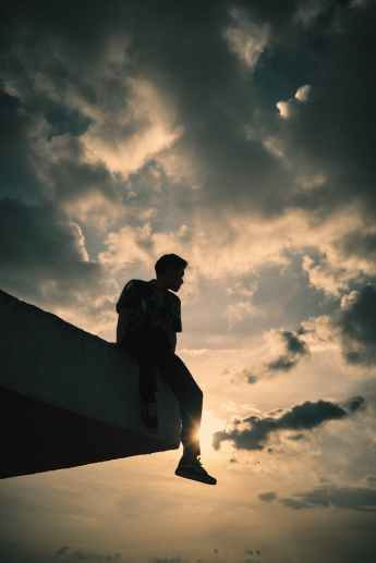 unrecognizable man sitting on rooftop edge against cloudy sundown sky, representing the loneliness of trying to stop drinking alcohol