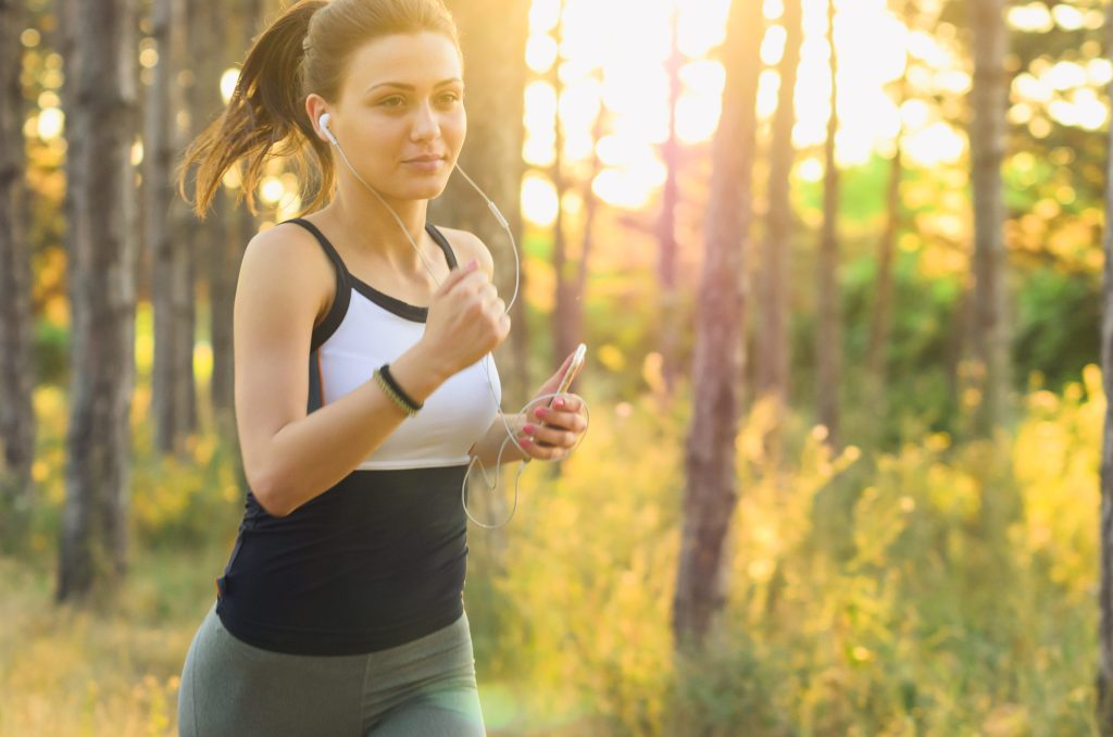 Woman running in woods with sunset behind her.