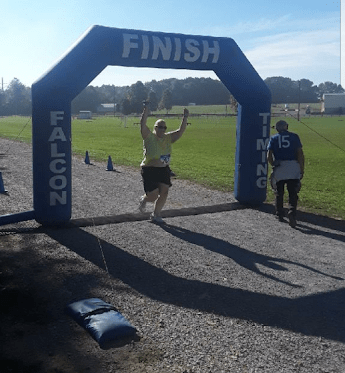 Nicky Bicksler crossing the finish line at her first 5k after surgery. She was running this race at three months post op. C25k makes running fun!