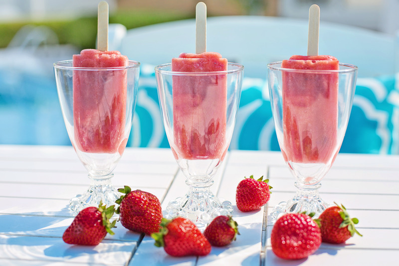 Three red ice pops in clear glasses with strawberries on a white table. Clear liquid diet: Post-bariatric surgery