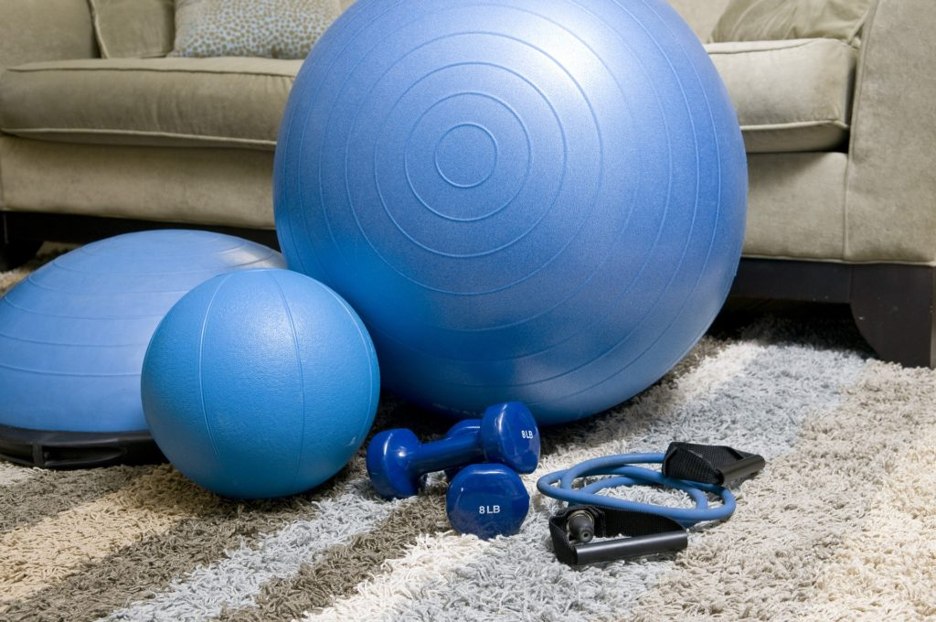 Blue bosce ball, medicine ball, exercise ball, hand weights, and resistance bands in living room. The benefits of starting a home gym.
