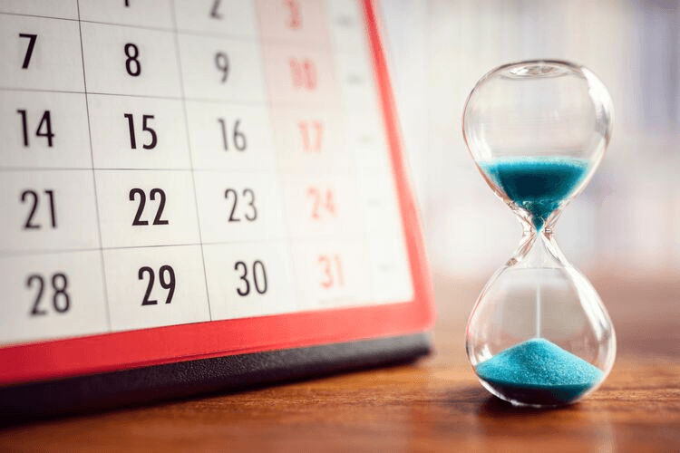 An hourglass with blue sand next to a calendar. 8 Smart Steps to Take Before Your Bariatric Surgery Date. Featured Image.