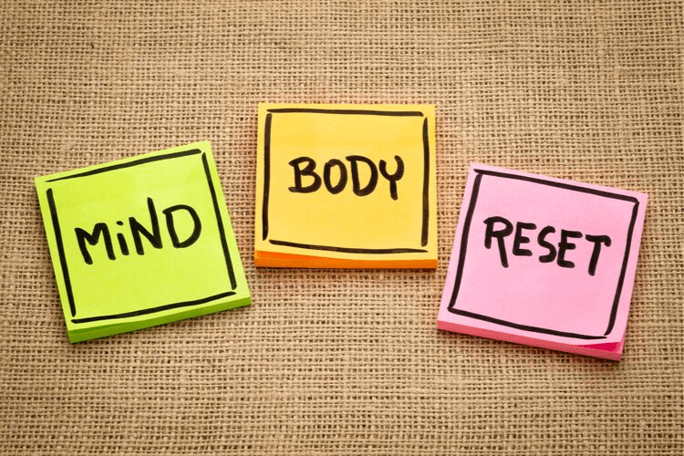 Three post-in notes on a brown table cloth with Mind Body Reset written on them. The Best Way to Reset Your Pouch | 5-Day Pouch Reset Vs. Intermittent Fasting | Featured Image