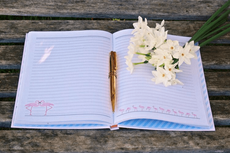 A white journal with flamingos and a gold pen and white flowers on a wooden deck. Journaling for Weight Loss | The Proven Way to Journal for Weight Loss | Featured Image