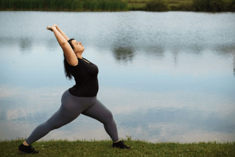 A woman doing a warrior position with bingo wings. Losing Your Bingo Wings | 7 Easy Exercises to Do at Home | Featured Image