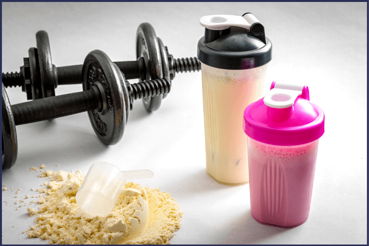 Two shaker cups of protein shakes with dumbbells and protein powder on the table. The Best High Protein Meal Replacement You'll Try | Bariatric Advantage