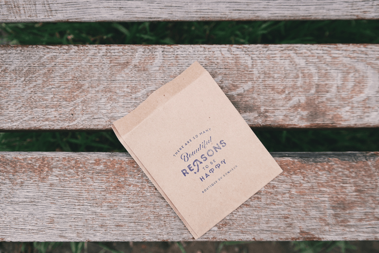 """A piece of paper with """"There are so many beautiful reasons to be happy"""" printed on it on top of wooden boards. How to be Grateful for Your New Life 