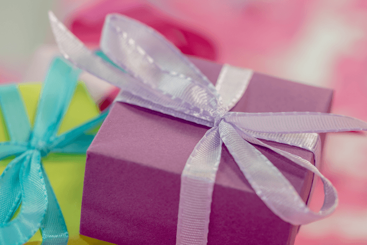 A pink gift with a light pink bow, a green gift with a teal bow in a pile. 20 Awesome Gifts for the Bariatric Patients in Your Life | Gifts They'll Love! | Featured Image