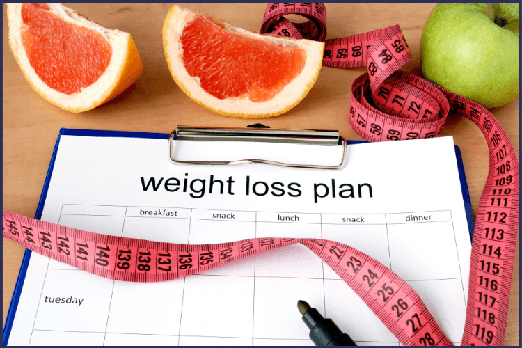 A weight loss plan on clipboard surrounded by a tape measure and fruit. How to Decide if the Bariatric Surgery Risks are Worth It | You are Worth It | Featured Image