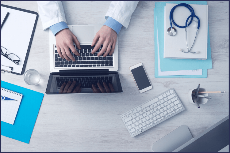 A doctor typing on a laptop with a stethoscope on top of a stack of papers on a desk. This is What Happens at the Pre-Op Consult for Bariatric Surgery + Final Testing | Featured Image