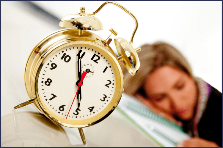 A woman sleeping in the background on a pile of book with a gold alarm clock pointing to 4:55. What to Expect at Your Overnight Sleep Study | Sleep Apnea Test | Featured Graphic | sleep apnea test, polysomnography, sleep study