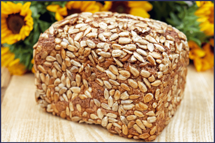 A loaf of whole-wheat bread surrounded by sunflowers. Simple Food Swaps for Weight Loss You Need to Make | Graphic | best food swaps for weight loss, healthy food swaps, simple food swaps