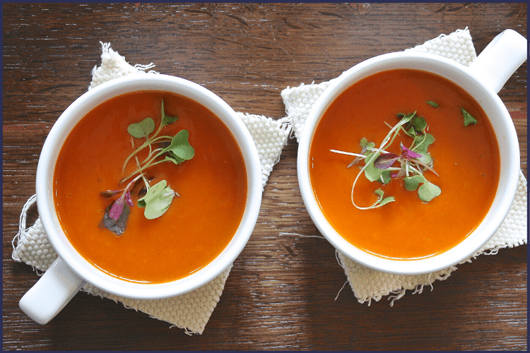 Two white cups of tomato soup topped with greens on a brown wooden table. | My Best Bariatric Liquid Diet Ideas You'll Want to Try | Plus Sample Menus | Graphic | full liquid diet, gastric sleeve full liquid diet