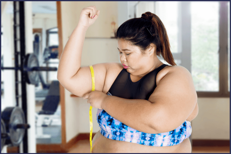 An obese Asian woman measures her bingo wings | How to Lose Your Bingo Wings in 7 Easy Exercises | Image | what causes bingo wings, bingo wings gif, how to lose your bingo wings
