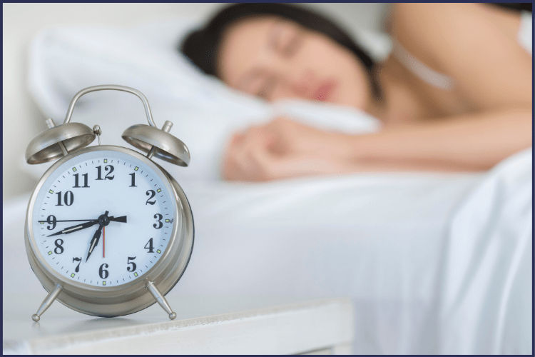 An alarm clock with a woman sleeping in the background. | 6 Easy Ways to Make a Bedtime Routine for Weight Loss | Make it a Habit | Image | bedtime yoga routine, nighttime exercises to lose weight