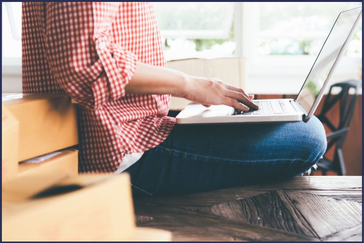 A woman in a red checkered shirt sitting cross-legged with a laptop on her lap. | The Opportunities You'll See at a Bariatric Surgery Information Session | Graphic | bariatric surgery program, free bariatric surgery, weight loss surgery