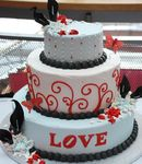 Three_tier_round_white_wedding_cake_with_black_beads_and_the_word_LOVE_in_red