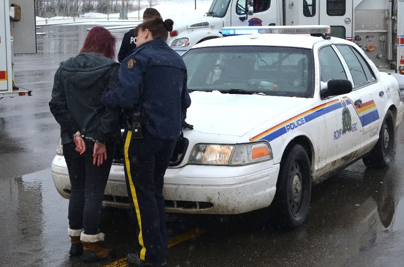 A student actor is put under arrest during a mock collision to educate students about the dangers of driving while drunk or distracted on Monday April 4, 2016 in Cold Lake, Alta. Peter Lozinski/Cold Lake Sun/Postmedia Network