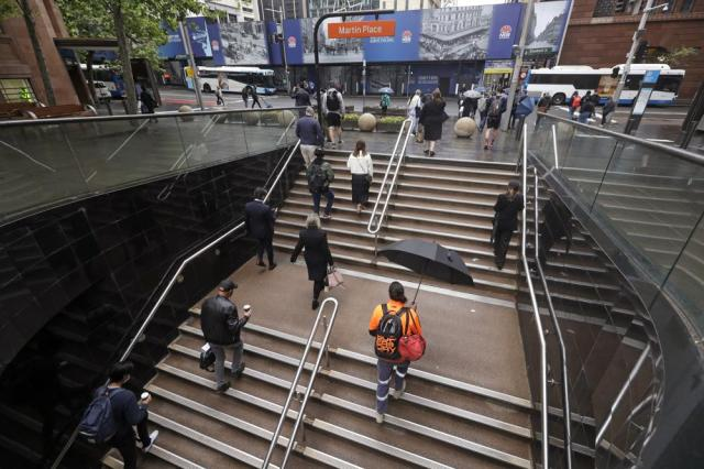 Commuters walk out of an underground train station as people filter into the city after more than 100 days of lockdown to help contain the COVID-19 outbreak in Sydney, Monday, Oct. 11, 2021. (AP Photo/Rick Rycroft)