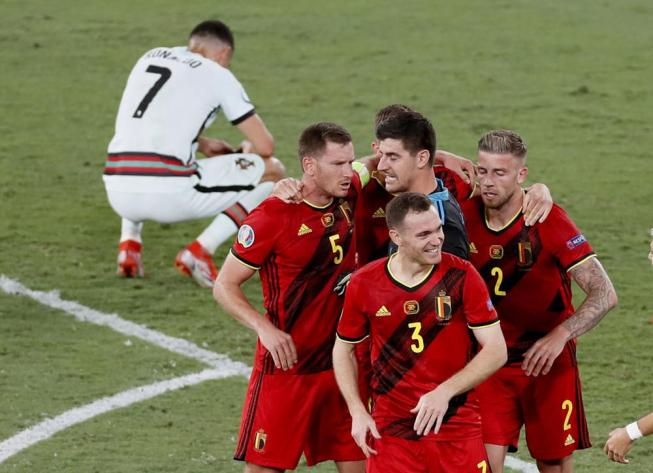 Belgium players celebrate winning 1-0 as Portugal's Cristiano Ronaldo, 7, reacts after the Euro 2020 soccer championship round of 16 match between Belgium and Portugal at La Cartuja stadium in Seville, Spain, Sunday, June 27, 2021. (Jose Manuel Vidal/Pool via AP)
