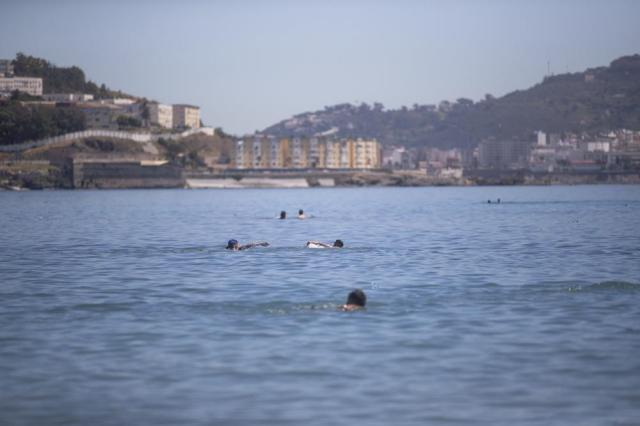 Moroccan boys swim from the Moroccan border town of Fnideq toward the Spanish enclave of Ceuta, on Wednesday, May 19, 2021. Thousands of would-be migrants converged on the Moroccan border town of Fnideq this week, part of an extraordinary mass effort to swim or scale barbed-wire fences to get into Spain for a chance at a new life. (AP Photo/Mosa'ab Elshamy)