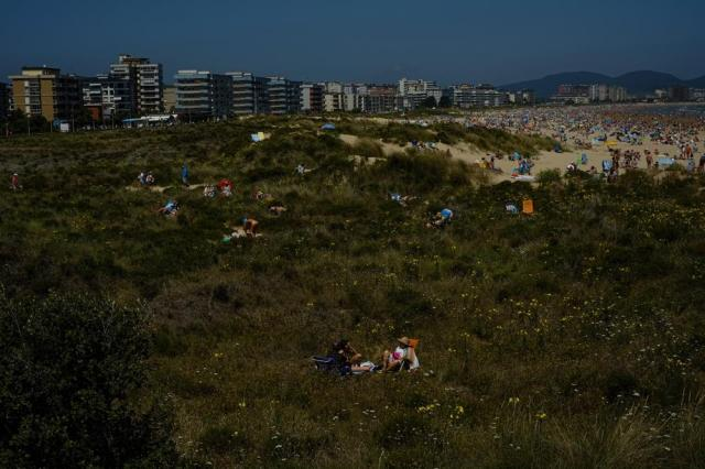 People sit close to the beach on a summer's day in Laredo, northern Spain, Saturday, July 17, 2021. (AP Photo/Alvaro Barrientos)