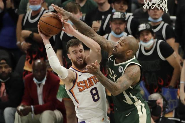 Phoenix Suns' Frank Kaminsky (8) is fouled by Milwaukee Bucks' P.J. Tucker during the second half of Game 3 of basketball's NBA Finals, Sunday, July 11, 2021, in Milwaukee. (AP Photo/Aaron Gash)