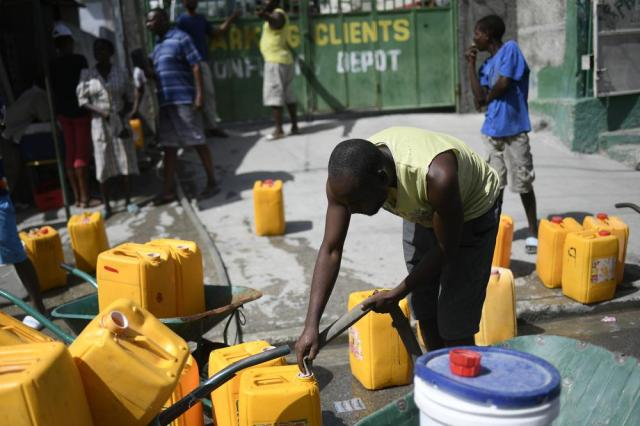 A man fills water tanks for sale in Port-au-Prince, Haiti, Sunday, July 11, 2021, four days after President Jovenel Moise was assassinated in his home. (AP Photo/Matias Delacroix)