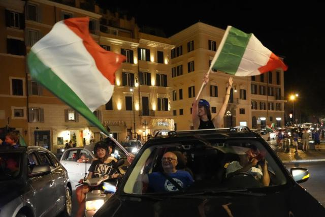 Italy's fans celebrate in Rome, Monday, July 12, 2021, after Italy beat England to win the Euro 2020 soccer championships in a final played at Wembley stadium in London. Italy beat England 3-2 in a penalty shootout after a 1-1 draw. (AP Photo/Gregorio Borgia)