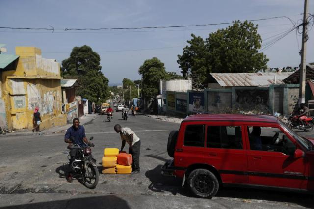 A man buys fuel fro his motorcycle at a street in Port-au-Prince, Haiti, Sunday, July 11, 2021, four days after President Jovenel Moise was assassinated in his home. (AP Photo / Fernando Llano)