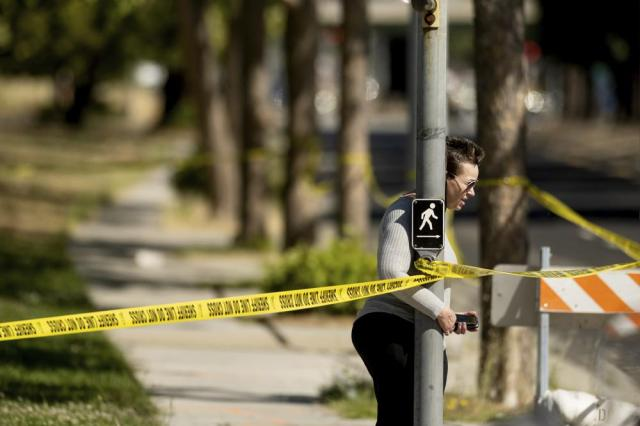 A woman leaves the scene of a shooting at a Santa Clara Valley Transportation Authority (VTA) facility on Wednesday, May 26, 2021, in San Jose, Calif. Santa Clara County sheriff's spokesman said the rail yard shooting left multiple people, including the shooter, dead. (AP Photo/Noah Berger)