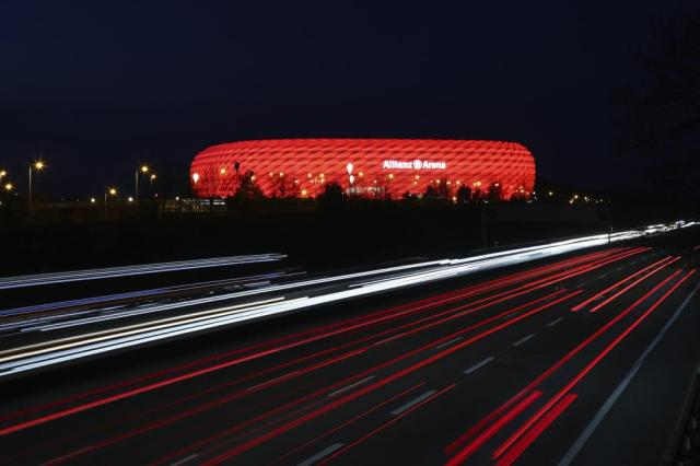 FILE - In this Monday, March 16, 2020 file photo, cars pass the illuminated 'Allianz Arena' soccer stadium in Munich, Germany. Hungary may play its final group game at the European Championship in a stadium lit up in rainbow colors.  Munich Mayor Dieter Reiter said Sunday June 20, 2021, he was going to write to UEFA to ask for permission for Germany's stadium to be lit up with the colors as a sign against homophobia and intolerance when the team plays Hungary on Wednesday. (AP Photo/Matthias Schrader, File)