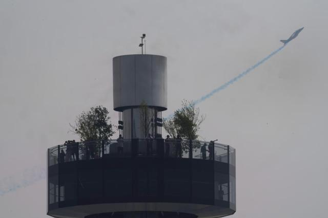 A member of the Patrouille de France military stunt team flies past the Garden in the Sky feature at Expo 2020 in Dubai, United Arab Emirates, Saturday, Oct. 2, 2021. (AP Photo/Jon Gambrell)