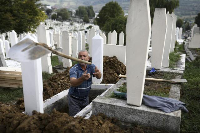 A man throws a shovel after digging graves for COVID-19 victims at the Bare cemetery in Sarajevo, Bosnia, Friday, Sept. 24, 2021. The COVID-19 rate of infections in Bosnia, a country where only about 12% of the population is fully vaccinated against COVID-19, is on a rising trend over the past weeks. (AP Photo)