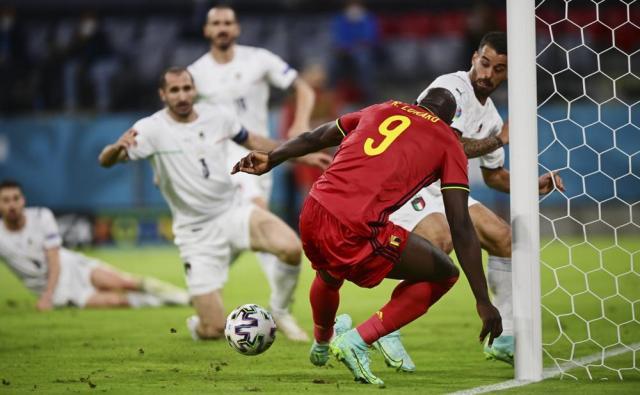 Belgium's Romelu Lukaku attempts a goal as Italy's Leonardo Spinazzola saves during the Euro 2020 soccer championship quarterfinal match between Belgium and Italy at at the Allianz Arena in Munich, Germany, Friday, July 2, 2021. (AP Photo/Philipp Guelland, Pool Photo via AP)