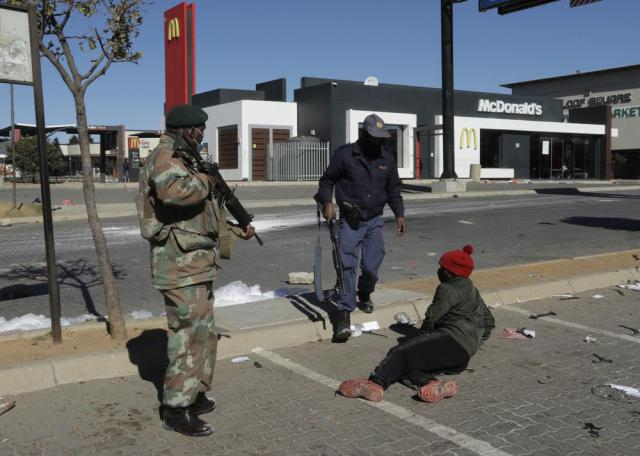 A policeman and soldier apprehend a looter at a shopping centre in Soweto, Johannesburg, Tuesday July 13, 2021. South Africa's rioting continued Tuesday with the death toll rising to 32 as police and the military struggle to quell the violence in Gauteng and KwaZulu-Natal provinces. The violence started in various parts of KwaZulu-Natal last week when Zuma began serving a 15-month sentence for contempt of court. (AP Photo/Themba Hadebe)