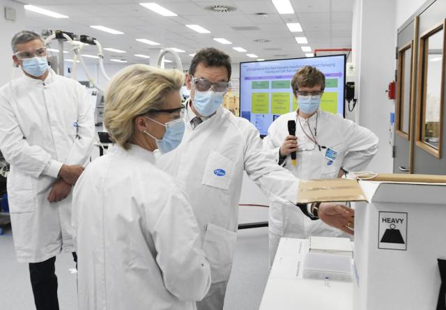 FILE - In this Friday, April 23, 2021 file photo, European Commission President Ursula von der Leyen, second left, speaks with Pfizer CEO Albert Bourla, center right, during an official visit to the Pfizer pharmaceutical company in Puurs, Belgium. The European Union cemented its support for Pfizer-BioNTech and its novel COVID-19 vaccine technology on Saturday, May 8, 2021 by agreeing to a massive contract extension for a potential 1.8 billion doses through 2023. The new contract, which has the backing of the EU member states, will entail not only the production of the vaccines, but also making sure that all the essential components should be sourced from the EU. (John Thys/Pool via AP, File)