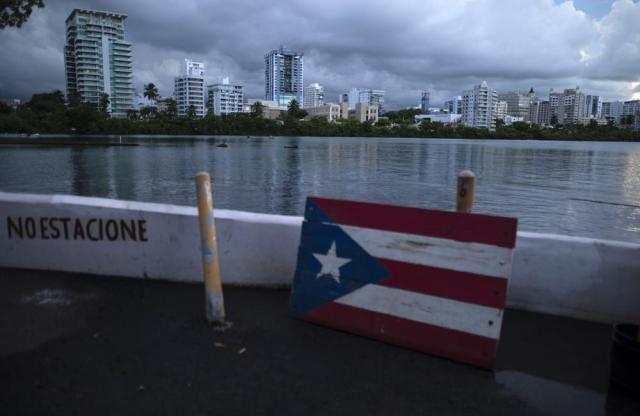 A wooden Puerto Rican flag is displayed on the dock of the Condado lagoon, where multiple selective blackouts have been recorded in the past days, in San Juan, Puerto Rico, Thursday, Sept. 30, 2021. Power outages across the island have surged in recent weeks, with some lasting up to several days. (AP Photo/Carlos Giusti)