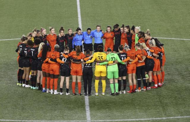 Portland Thorns and Houston Dash players, along with referees, gather at midfield, in demonstration of solidarity with two former NWSL players who came forward with allegations of sexual harassment and misconduct against a prominent coach, during the first half of an NWSL soccer match in Portland, Ore., Wednesday, Oct. 6, 2021. (AP Photo/Steve Dipaola)