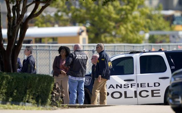 Law enforcement officers from different agencies gather in the parking lot of Timberview High School after a shooting inside the school located in south Arlington, Texas, Wednesday, Oct. 6, 2021. (AP Photo/LM Otero)