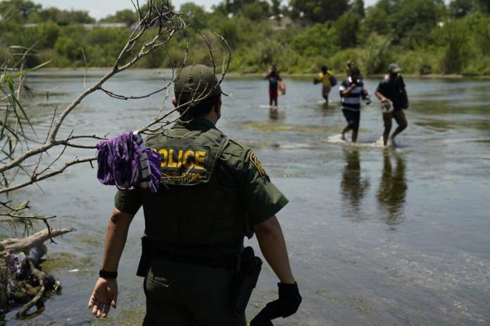 A Border Patrol agent watches as a group of migrants walk across the Rio Grande on their way to turn themselves in upon crossing the U.S.-Mexico border, Tuesday, June 15, 2021, in Del Rio, Texas. U.S. government data shows that 42% of all families encountered along the border in May hailed from places other than Mexico, El Salvador, Guatemala and Honduras — the traditional drivers of migratory trends. (AP Photo/Eric Gay)